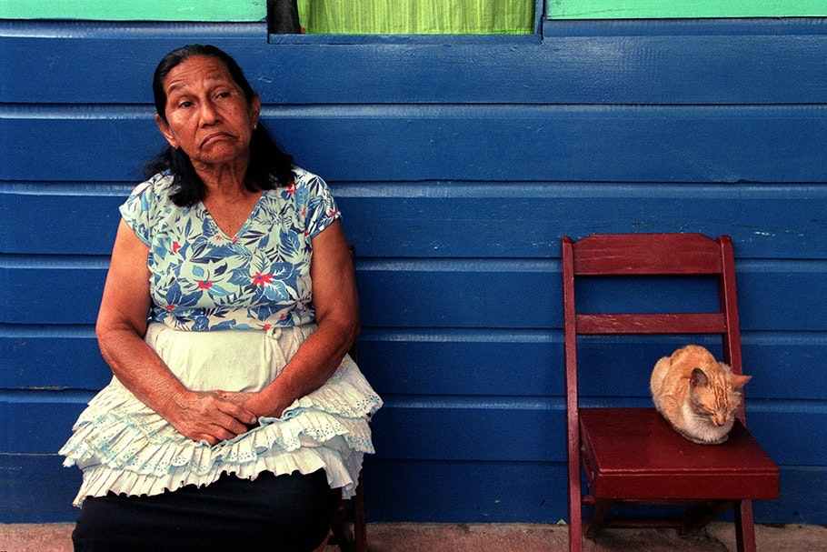 A woman and a cat seated in front of a blue wall.