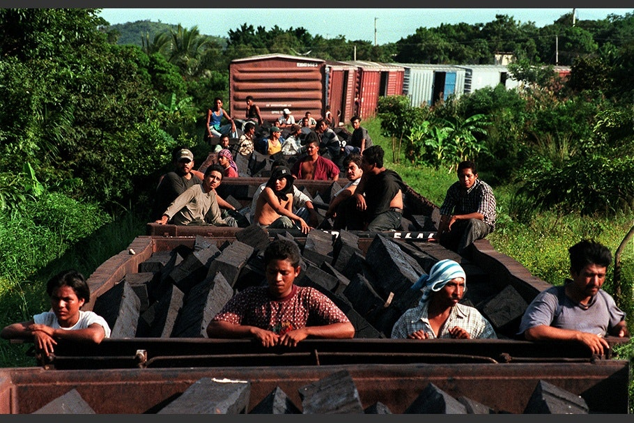 People riding on a freight train.