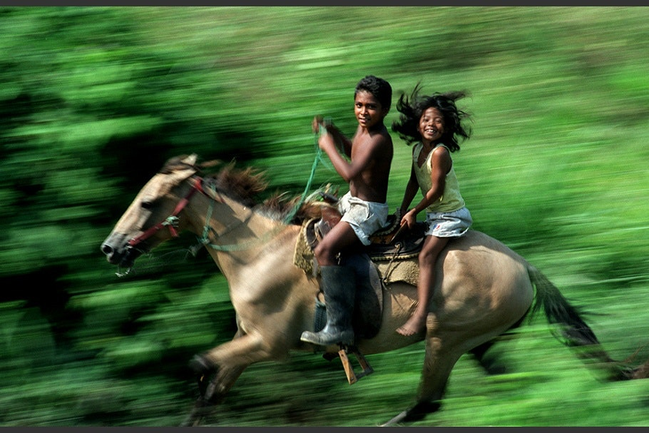 Two children riding a horse.
