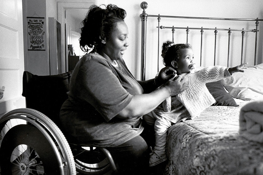 A mother in a wheelchair with a toddler on a bed.