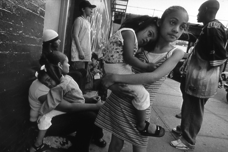 Teenagers and children on a sidewalk.