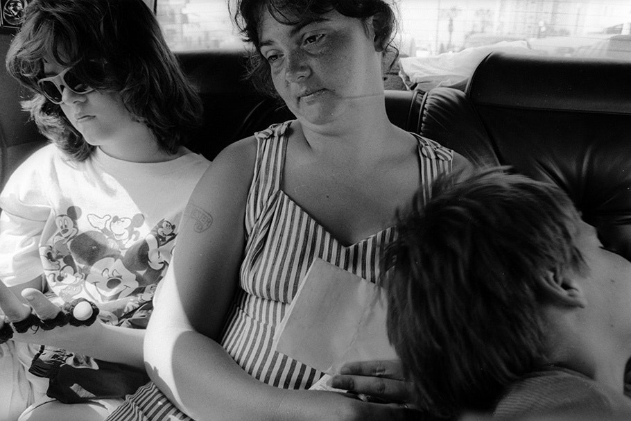 A woman and two children in the backseat of a car.