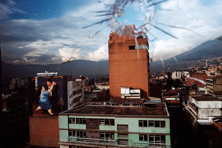 A cityscape viewed through glass with a bullet hole.
