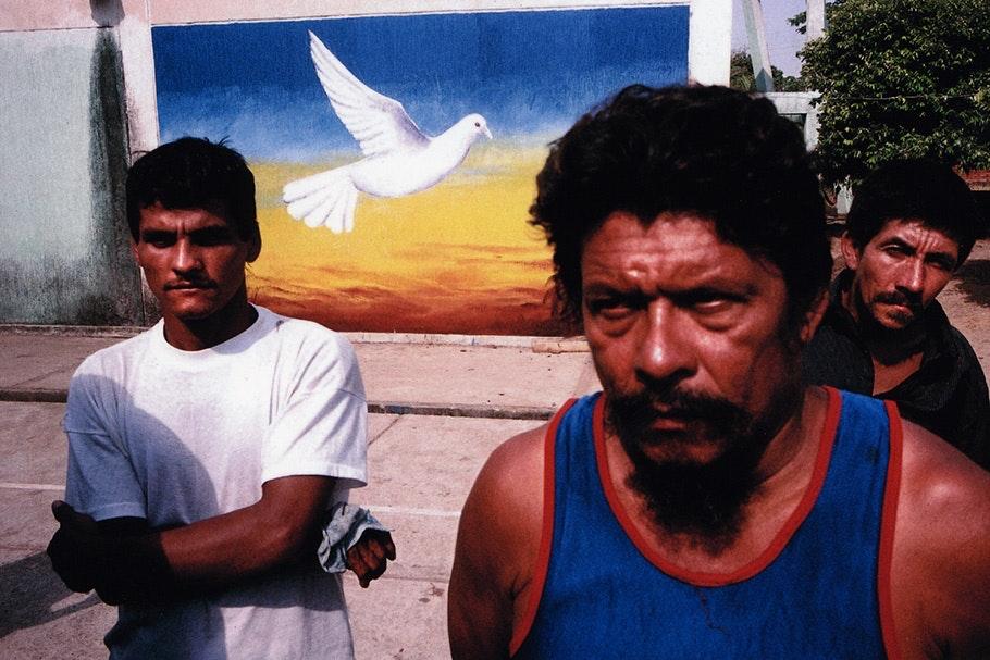 Men in front of a dove mural.