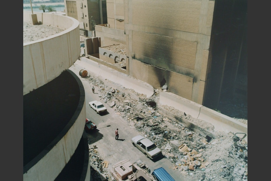 A curved building and a ruined street, viewed from above.