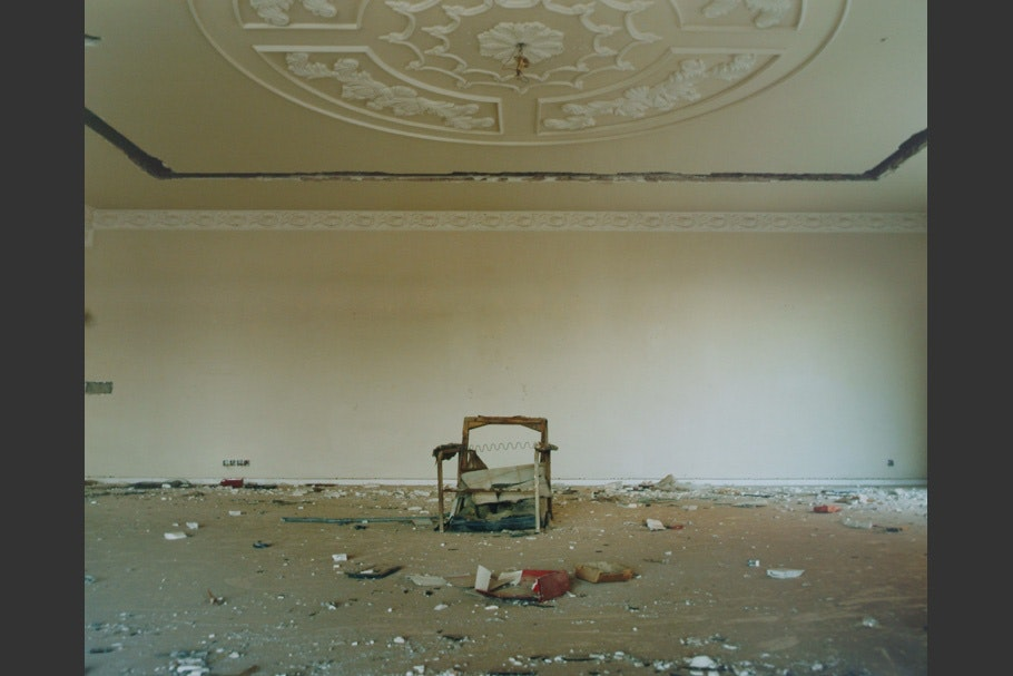 Ruined chair beneath an ornate ceiling.