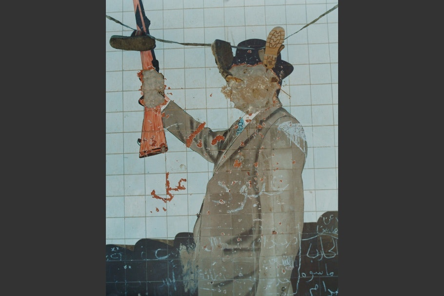 Defaced mural of Sadam Hussein.