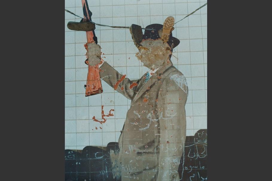 Defaced mural of Sadam Hussein.