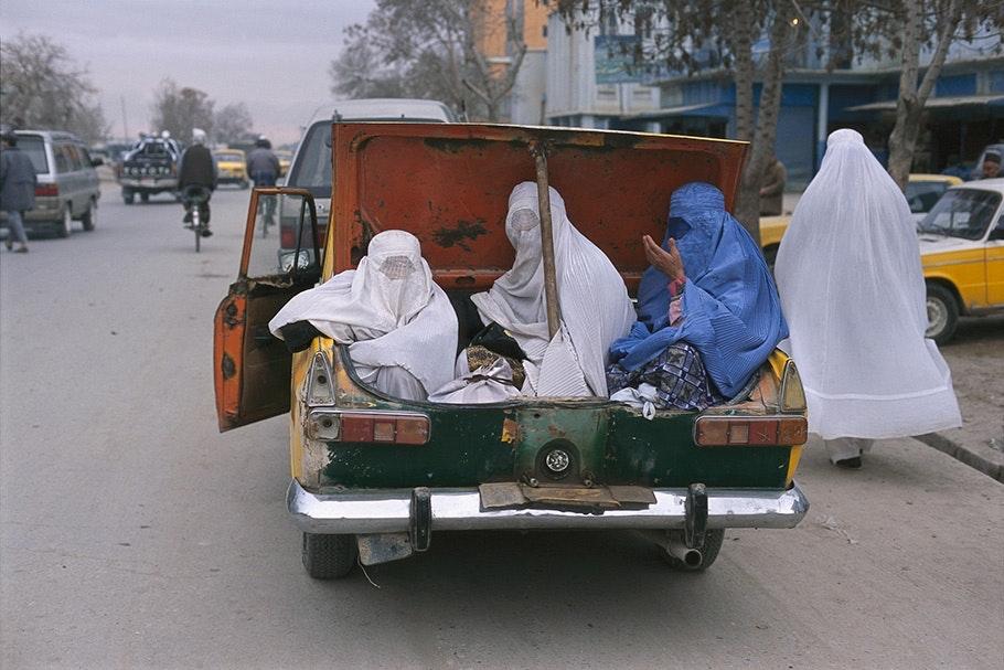 Women in burqas sitting in the trunk of a car.