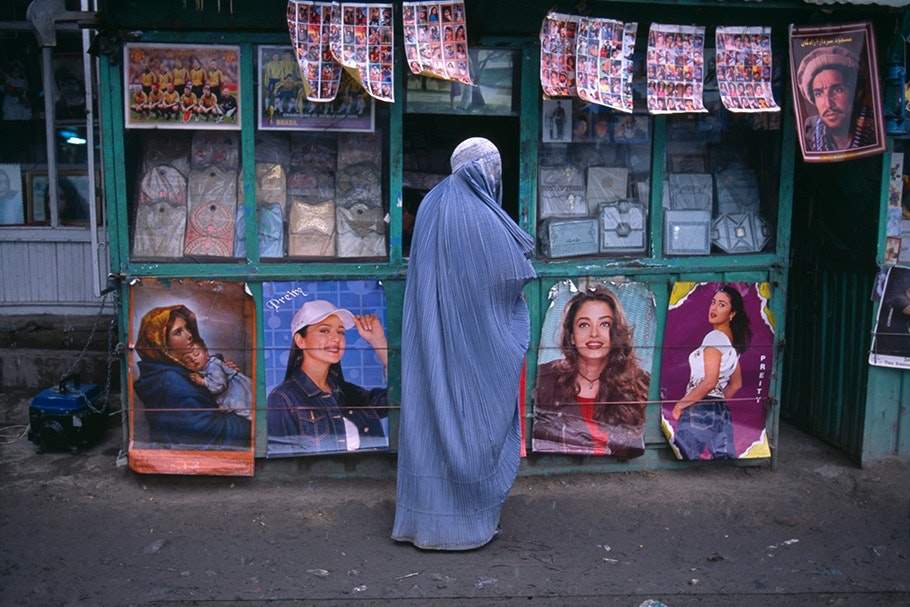 A woman in a burqa in front of movie posters.