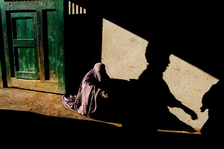 A woman begging in front of a sun and shadow streaked wall.