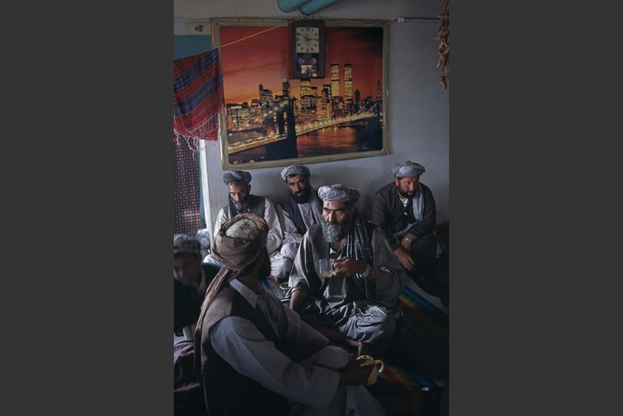 Men in a tea house below a New York City poster.