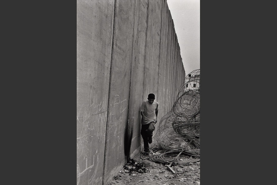 A boy runs between the wall and razor wire.