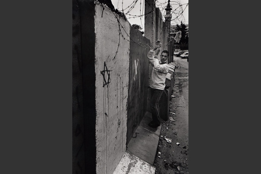 A boy walks along the wall with a painted Star of David.