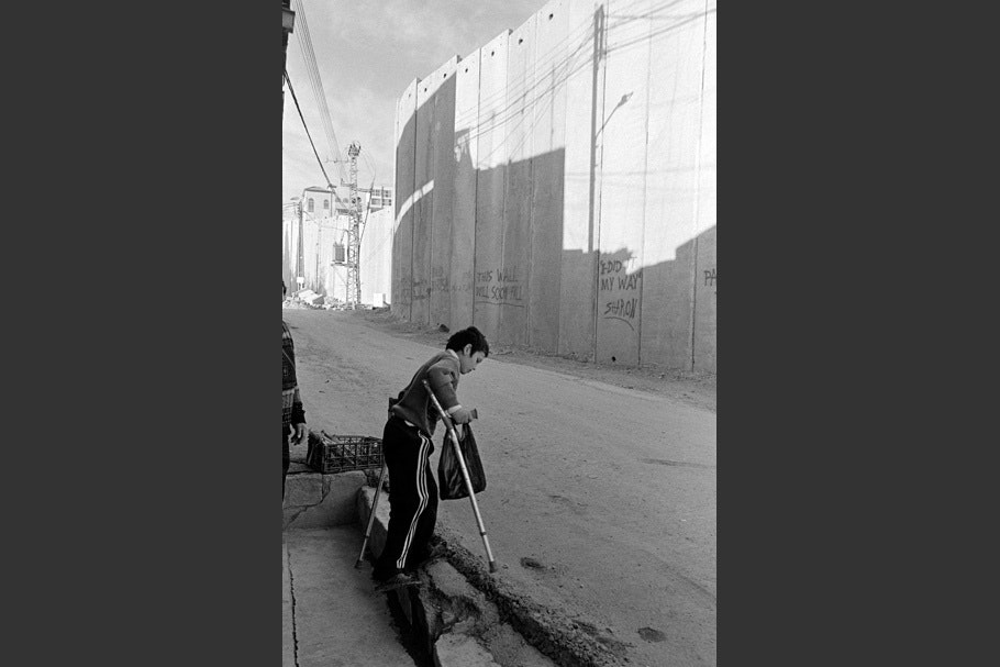 A boy with crutches walking near the wall.