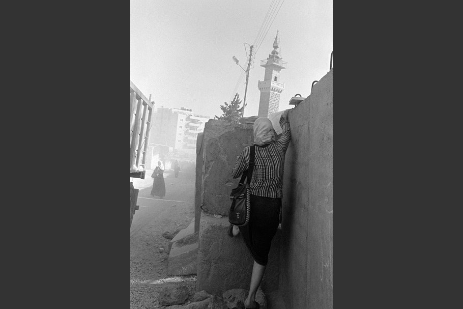 A woman in a striped shirt walking next to wall.