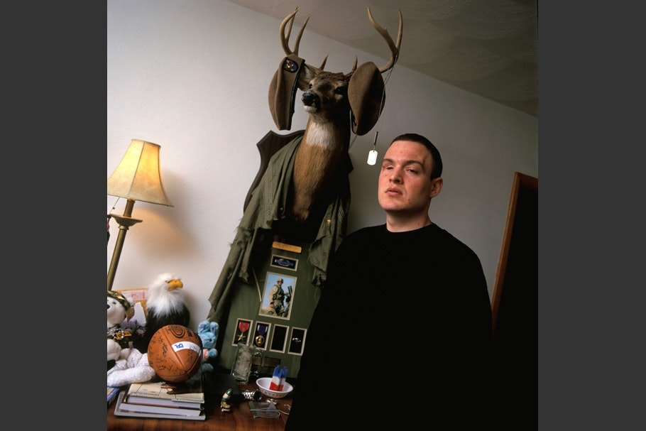 Soldier in front of a stuffed deer head.