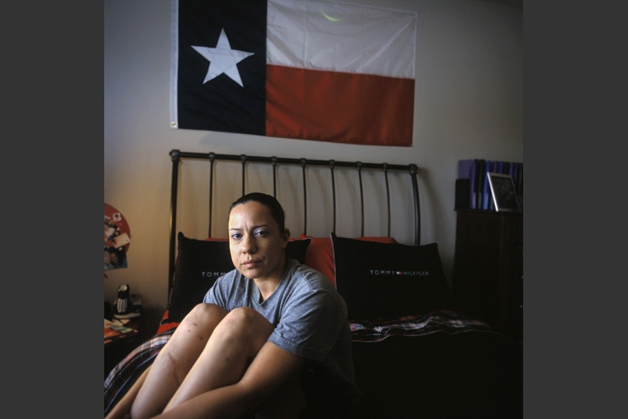 Female soldier sitting on bed under Texan flag.