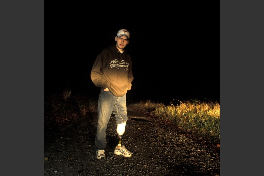 Soldier with prosthetic leg outside at night.