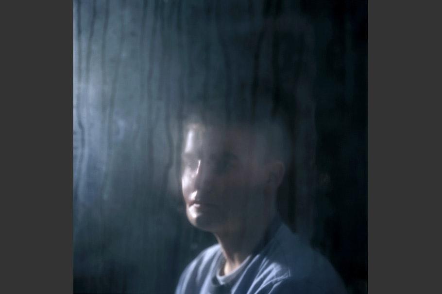 Soldier viewed through fogged window.
