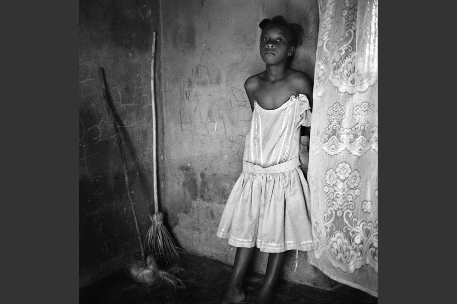 Girl posing in white dress next to brooms.