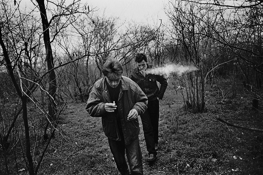 Two men smoking outside.