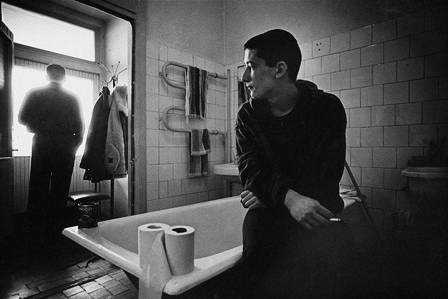 A man sitting on a bathtub and another looking out a window.