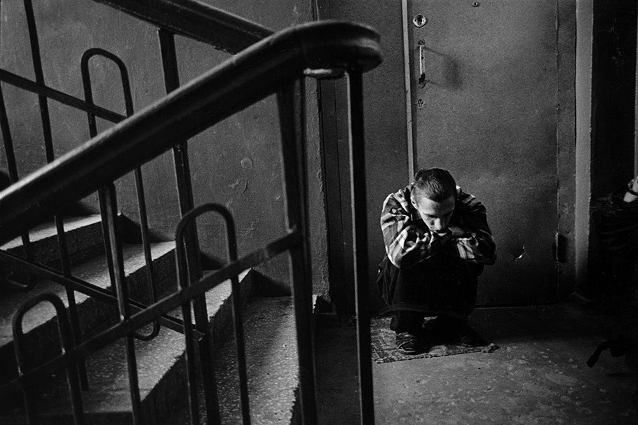 A man crouched in a stairwell.
