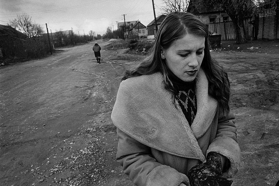 A woman in a winter coat walking down a street.