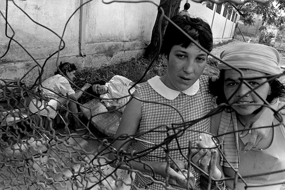 Four people seen through a bent chainlink fence.