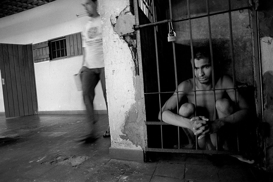 A teenage boy in a small cell behind bars.