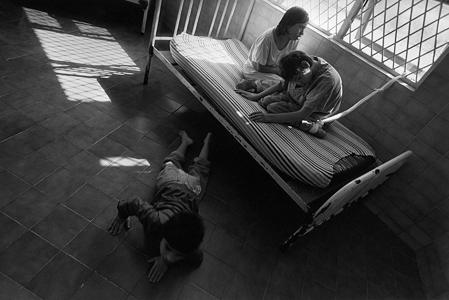 Two children on a bed and one on the floor.