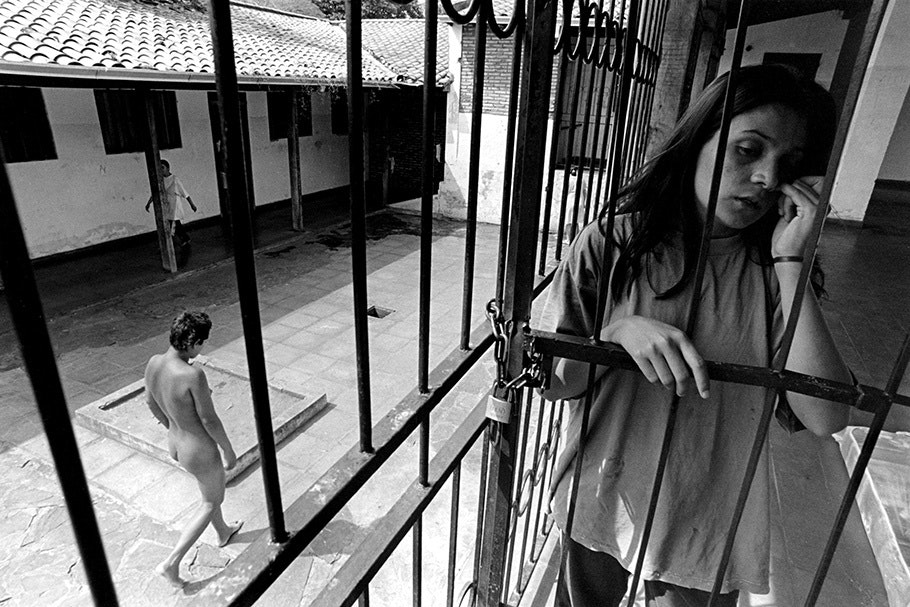 A woman behind bars, while another walks by unclothed.