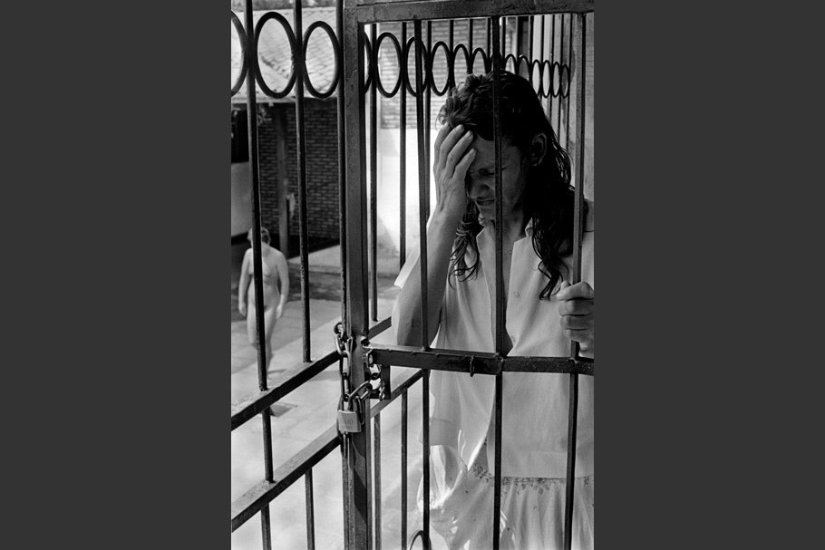 A vertical of a woman behind bars with her hand on her face.