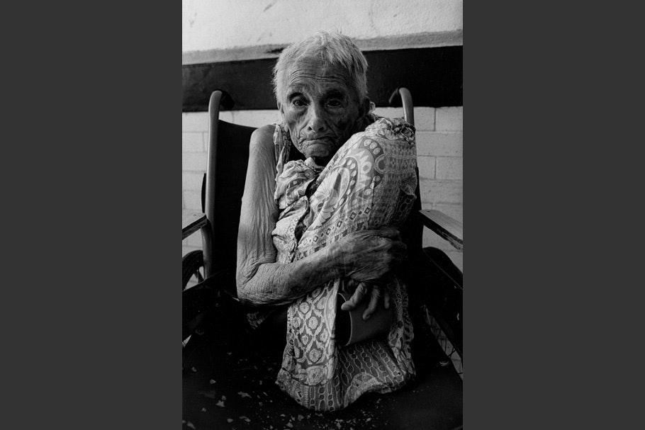 An elderly woman in a wheelchair.