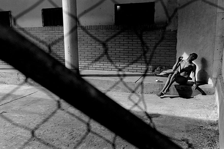 A patient, viewed through bent chicken wire, sitting in the sun.