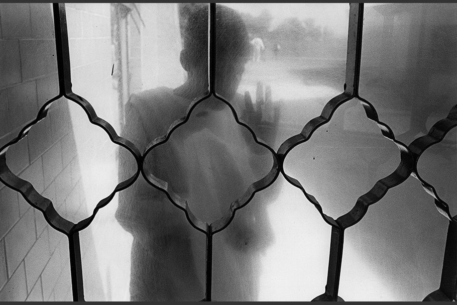 A patient viewed through frosted glass and patterned bars.