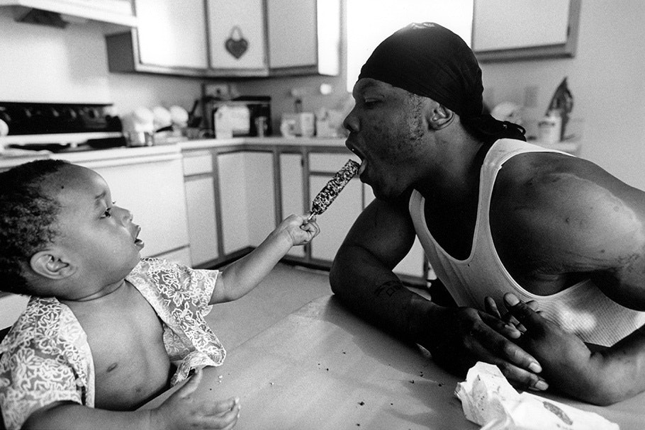 An infant feeding his father a popsicle.