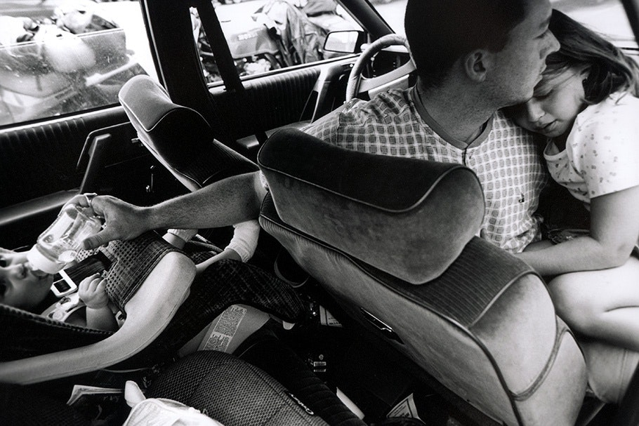 A father in a car feeds a child and holds another.