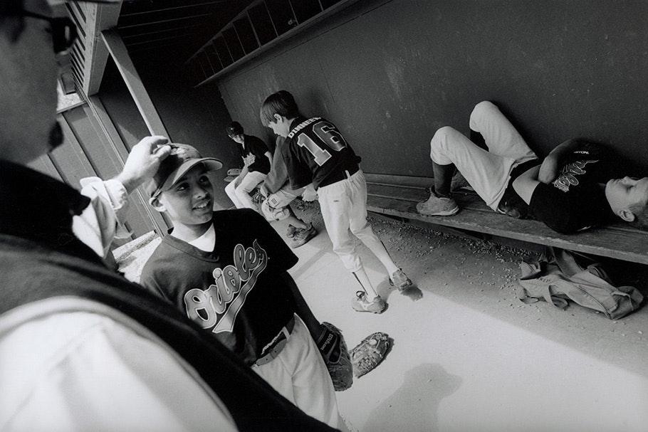 Little league baseball players in a dugout.