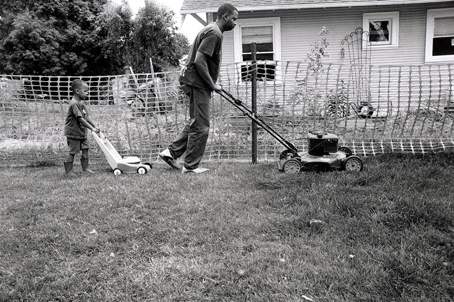 A man with a lawnmower and a boy with a toy lawnmower.