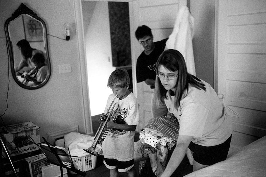 Parents folding laundry and a boy playing trombone.