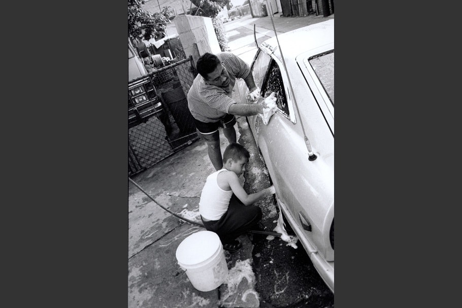 A father and son wash a car together.