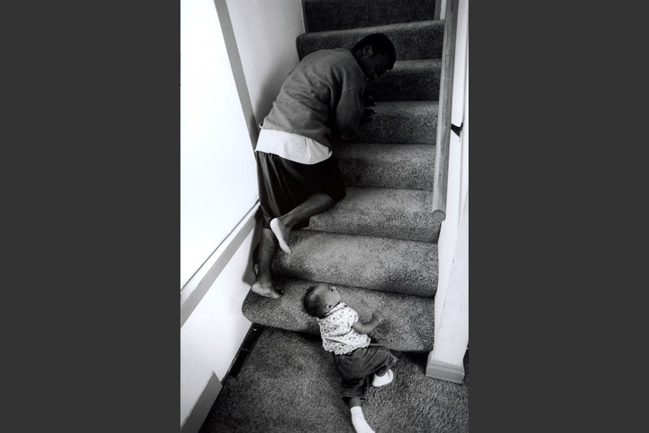 A father and infant climb up stairs.