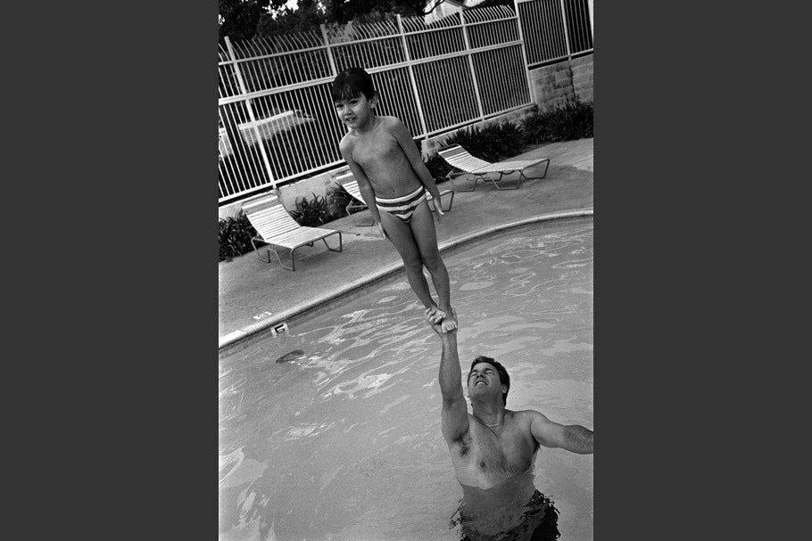 A father lifting up his son in a pool.