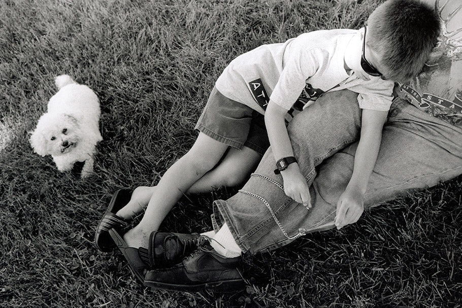 Father and son in the grass with a dog.