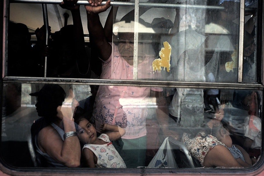 People viewed through a bus window.