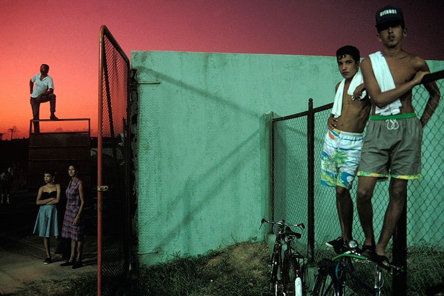 Five teens with a fence, a wall, bikes, and a red sky.