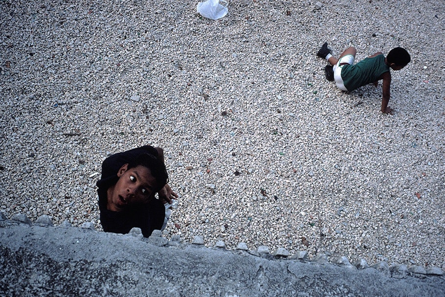 A boy looking through a hole and another on the ground.