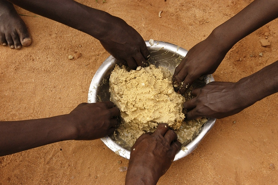 Hands reaching into a bowl of food.